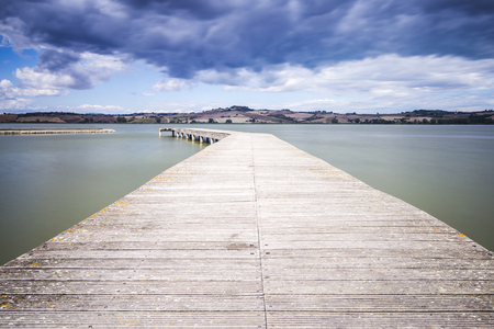 Wooden dock on Lake Chiusi in Tuscany in Italy