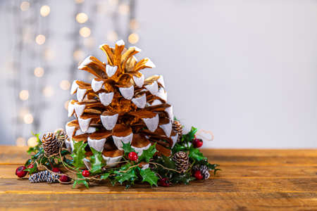 The materials to create a X-mas corner: a gold and white painted pine cone, holly leaves with red berries and little pine cones, a sparkling lights in the background to enhance the wintry atmosphere. Stock fotó