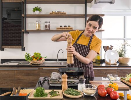 Young housewife putting pepper on the steak. Morning atmosphere in a modern kitchen. The kitchen counter full of various kinds of vegetables and seasonings.