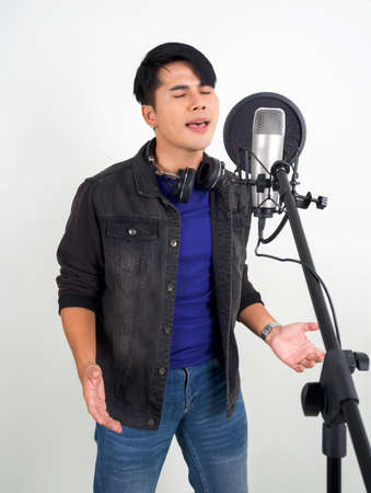 Young asian man with headphones singing with microphone. Portrait on white background with studio light. Reklamní fotografie