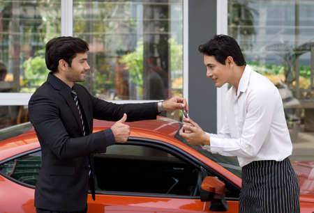 A Persian businessman in a black suit smiles and thumbs up while handling sport car key to the valet service staff.