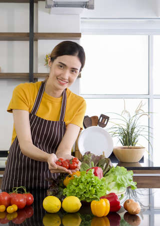 Young asian housewife holding red tomatoes with both hands. The Basket full of various kinds of vegetables. Morning atmosphere in a modern kitchen. Banque d'images