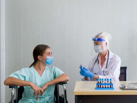 An old woman doctor with a face shield and a protection mask inform the temperature measured result to the patient sitting in a wheelchair. Banque d'images