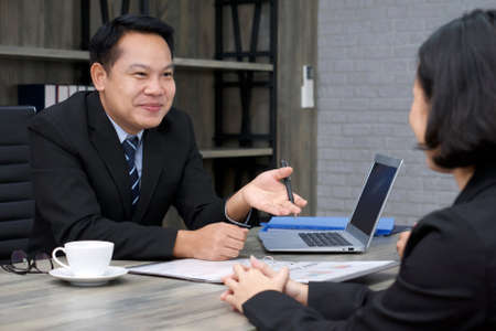 Asian manager in the black suit interviewed the applicant with a smile. The atmosphere of job interview in the modern office.