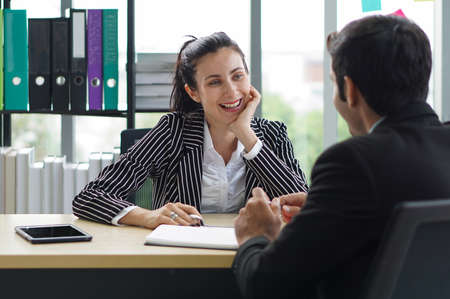 Young business woman in a black suit smiled and laughed happily during the meeting. Morning work atmosphere In a modern office.