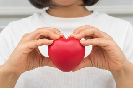 Woman in white shirt holding red love heart