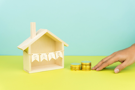 buying a house concept, hand pushing two stacks of golden coins toward a wooden house model with sale sign