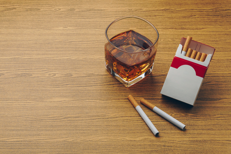 a glass of bourbon whiskey, two cigarettes with a cigarette pack on the wooden table