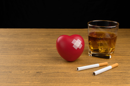 unhealthy lifestyle concept, red heart symbol with adhesive plaster, two cigarettes and a glass of bourbon whiskey on wooden table