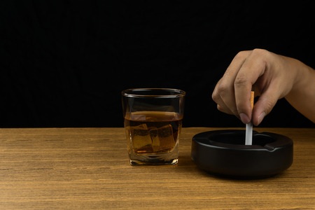 hand stubbing out a cigarette on the black ceramic ashtray, a glass of bourbon whiskey on wooden table.