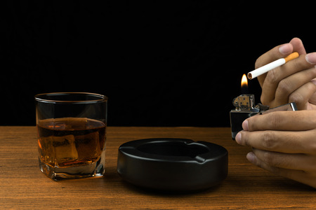 hand lighting up a cigarette, black ceramic ashtray and a glass of bourbon whiskey on wooden table.
