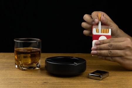 hand taking a cigarette from pack. a glass of bourbon whiskey, a black ceramic ashtray and a chrome lighter on wooden table.