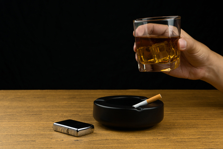 hand holding a glass of bourbon whiskey, a cigarette in the black ceramic ashtray and the chrome lighter on wooden table.