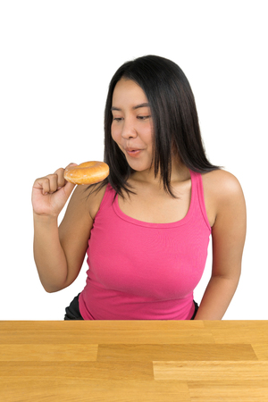 beautiful plus size Asian woman sitting at the wooden table and holding a doughnut on white background