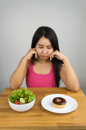 beautiful plus size Asian woman choosing between salad and chocolate doughnut, dieting concept
