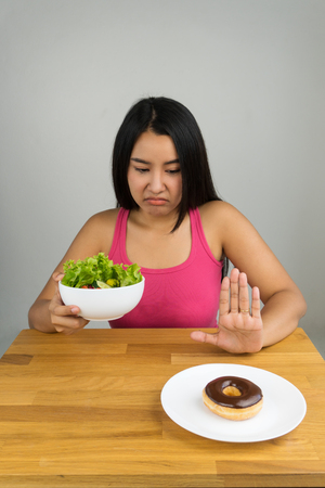 beautiful young Asian woman choosing salad bowl and rejecting chocolate doughnut, dieting concept