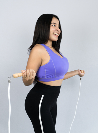 young and beautiful Asian woman in sportswear skipping with jump rope, fat burning workout indoor