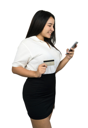 Online shopping concept, a beautiful Asian woman holding a credit card and looking at her smartphone, isolated on white background.