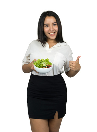 beautiful plus size Asian woman holding a bowl of salad and showing thumb up, isolated on white background