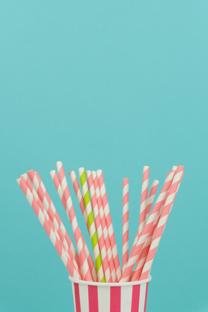 green and pink striped straws in a party paper cups with blue background
