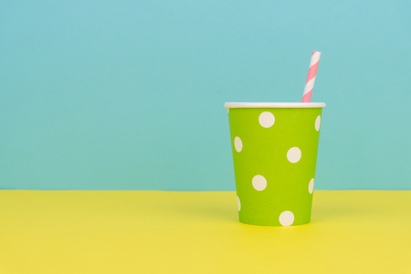 a green polka dot party paper cup with pink striped straw on the yellow table with blue background