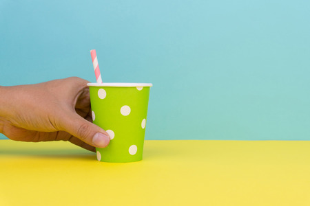 hand holding a green polka dot party paper cup with pink striped straw, yellow table with blue background 免版税图像