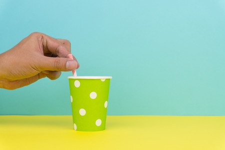 put a pink striped straw into a green polka dot party paper cup, yellow table with blue background