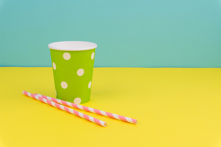 green polka dot party paper cup and pink striped straws on yellow table with blue background