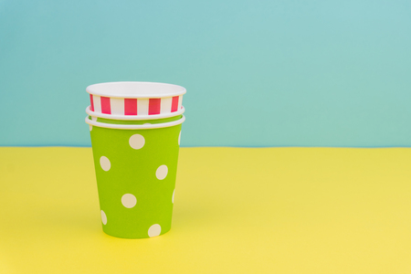 stack of colorful party paper cups on yellow table with blue background