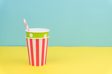 colorful party paper cups and striped straw on yellow table with blue background