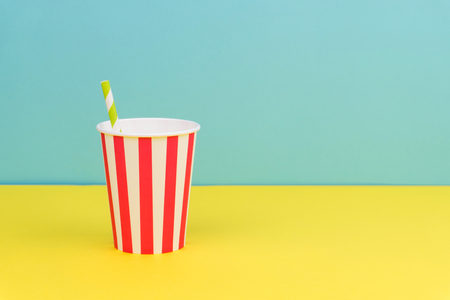 a striped party paper cup with green striped straw on the yellow table with blue background