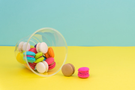 colorful mini macarons in plastic cup on yellow table with blue background 免版税图像