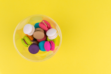 Top view of colorful mini macarons in plastic cup on yellow table 免版税图像