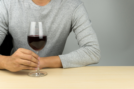 man in grey shirt with a glass of red wine at the wooden table