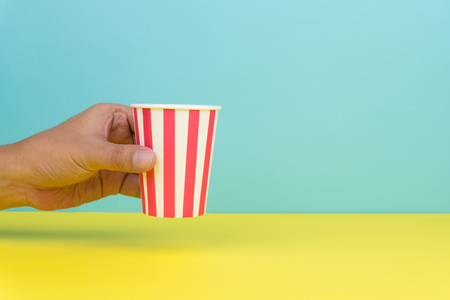 hand holding a colorful party paper cup, yellow and blue background