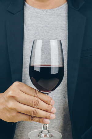 man in grey shirt and black suit holding a glass of red wine