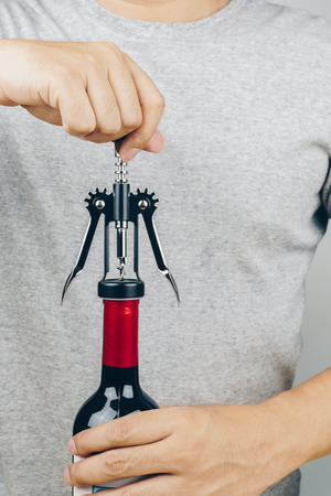 man in grey shirt opening a red wine bottle with a metal corkscrew 免版税图像