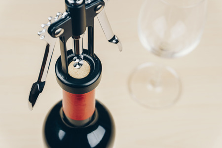 opening a red wine bottle with a corkscrew, empty wine glass on the wooden table 免版税图像