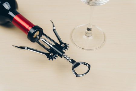 a red wine bottle with a metal corkscrew and an empty wine glass on the wooden table 免版税图像