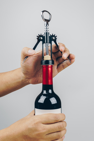 close up of hands opening a red wine bottle with a metal corkscrew