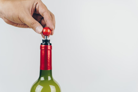 close up of hand using a wine stopper to close a red wine bottle