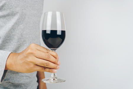 man in grey shirt holding a glass of red wine, white background