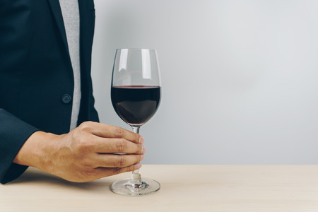 man in grey shirt and black suit putting a glass of red wine on the wooden table