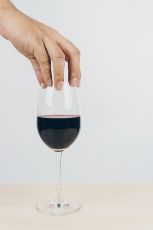 hand putting a glass of red wine on the wooden table