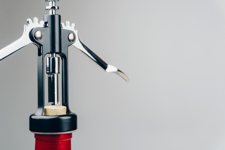 close up of a metal corkscrew with a bottle of red wine 免版税图像