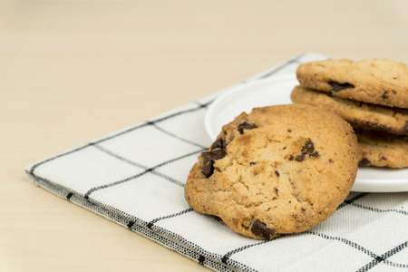 the chocolate chip cookies in a white round dish on the cloth at the wooden table. 免版税图像