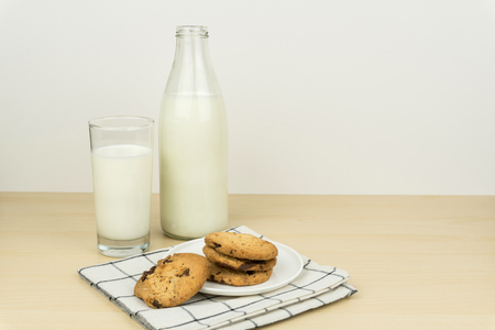 a glass of milk with milk bottle and the chocolate chip cookies in a white round dish on the wooden table.