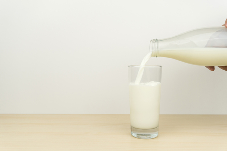 hand pouring milk from the bottle into a glass