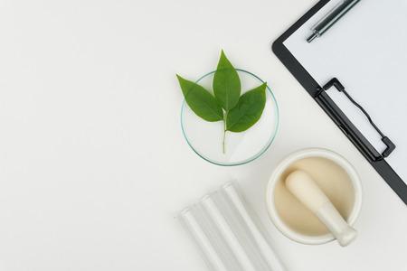 Forschungskonzept der Kräutermedizin. die organischen grünen Blätter im Uhrglas mit Mörser und Stößel, drei Reagenzgläser und ein Klemmbrett mit einem Stift auf dem weißen Tisch im Labor.