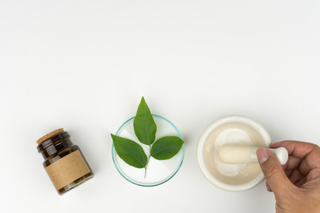 herbal medicine concept. pharmacist using a mortar and pestle, the organic green leaves in watch glass with a bottle on the white table in laboratory. 免版税图像